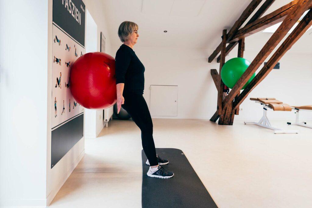 Startposition Kniebeuge an der Wand mit Gymnastikball