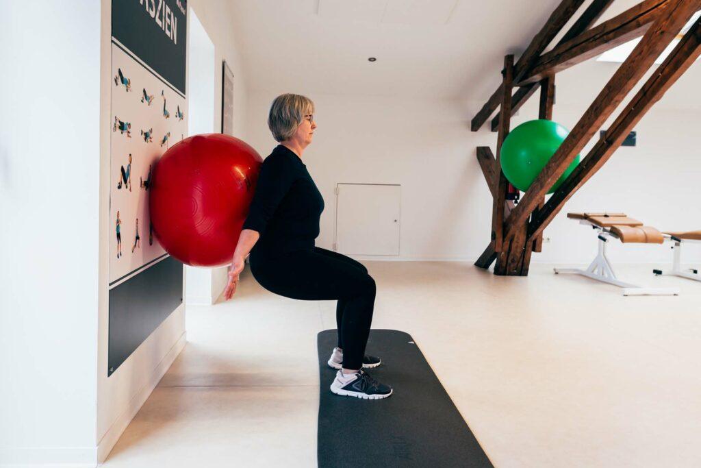 Endposition Kniebeuge an der Wand mit Gymnastikball
